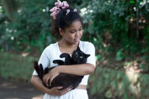 Girl is holding a black cat